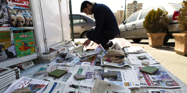 EDITORS' NOTE: Reuters and other foreign media are subject to Iranian restrictions on leaving the office to report, film or take pictures in Tehran. A man looks at newspapers at a news stand in Tehran March 4, 2012. Hardliners allied with Iran's Supreme Leader Ayatollah Ali Khamenei maintained their lead in the country's parliamentary vote, with partial results on Sunday showing supporters of the president trailing behind. REUTERS/Raheb Homavandi  (IRAN - Tags: POLITICS ELECTIONS)