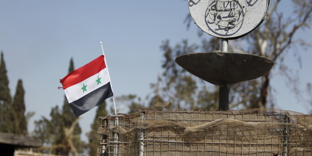 A Syrian national flag flutters next to the Islamic State's slogan at a roundabout where executions were carried out by ISIS militants in the city of Palmyra, in Homs Governorate, Syria in this April 1, 2016 file photo. To match MIDEAST-CRISIS/SYRIA- INSIGHT REUTERS/Omar Sanadiki/Files
