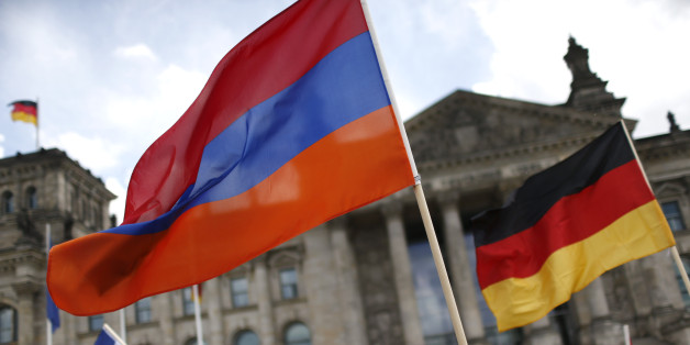 "Supporters wave Armenian and German flags in front of the Reichstag, the seat of the lower house of parliament Bundestag in Berlin, Germany, June 2, 2016, as they protest in favour of approval of a symbolic resolution by Germany's parliament that declares the 1915 massacre of Armenians by Ottoman forces a ""genocide"".  REUTERS/Hannibal Hanschke"