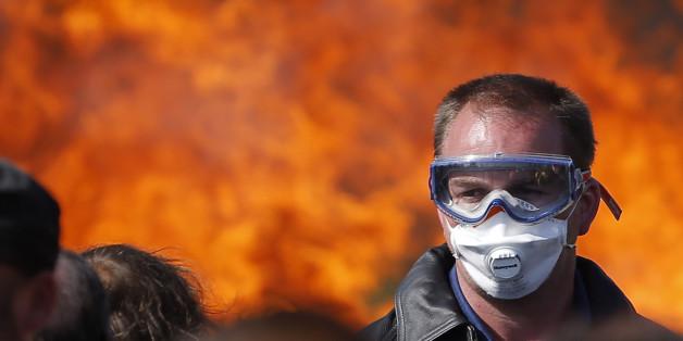 Ein französischer Gewerkschaftsangehöriger vor einer brennenden Barrikade in Donges