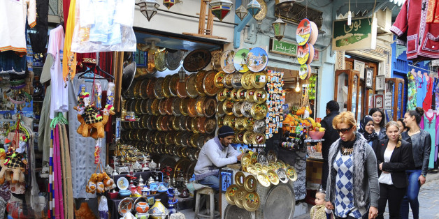 Tunisians walk in a market of Tunis, Friday, March 20, 2015. Yet another terror attack is taking its toll on tourism, with cruise companies cancelling stops in Tunisia following the killings of 21 people. Seventeen of those killed at the Bardo National Museum in Tunis were passengers on shore excursions from two cruise ships in port that day. (AP Photo/Salah Ben Mohamed)