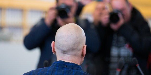 Der Angeklagte Frank S. hält sich einen Aktendeckel vor das Gesicht.