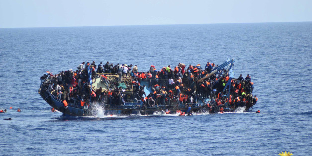 """Migrants are seen on a capsizing boat before a rescue operation by Italian navy ships """"Bettica"""" and """"Bergamini"""" (unseen) off the coast of Libya in this handout picture released by the Italian Marina Militare on May 25, 2016. Marina Militare/Handout via REUTERS/File Photo    ATTENTION EDITORS - THIS PICTURE WAS PROVIDED BY A THIRD PARTY. FOR EDITORIAL USE ONLY."""