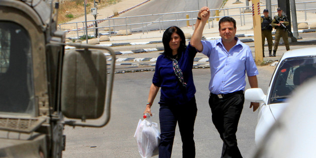 Palestinian lawmaker Khalida Jarrar (L) holds the hand of Arab-Israeli Knesset member Ayman Odeh following her release from an Israeli jail at Israeli Jbara checkpoint near the West Bank city of Tulkarm June 3, 2016. REUTERS/Abed Omar Qusini
