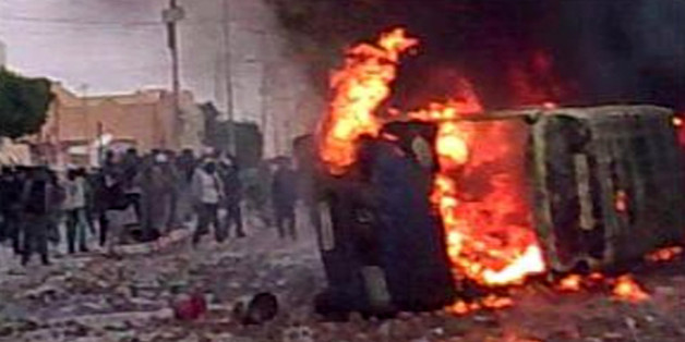 In this frame grab image taken from amateur video and acquired by APTN  protesters are seen amid a burning vehicle in Douz, Tunisia, Wednesday Jan. 12, 2011. A witness in the central city of Douz said there were two deaths at a protest there Wednesday.  Tear gas and stone-throwing youths reached the heart of Tunisia's once-calm capital Wednesday as rioters desperate for jobs defied their autocratic president in escalating unrest that poses his biggest challenge in 23 years in power. (AP Photo)