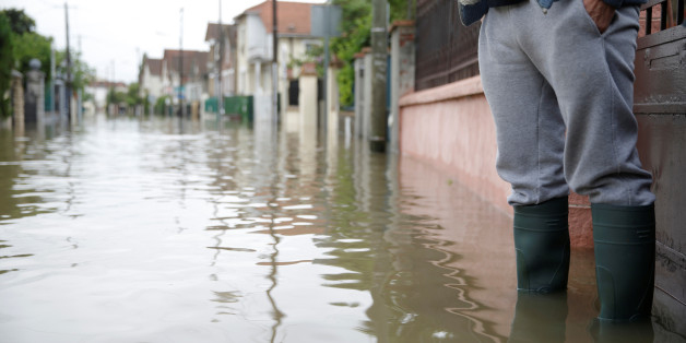 A resident stands in front of his house in a flooded suburb of Villeneuve Saint-Georges, outside Paris, June 3, 2016. REUTERS/Christian Hartmann