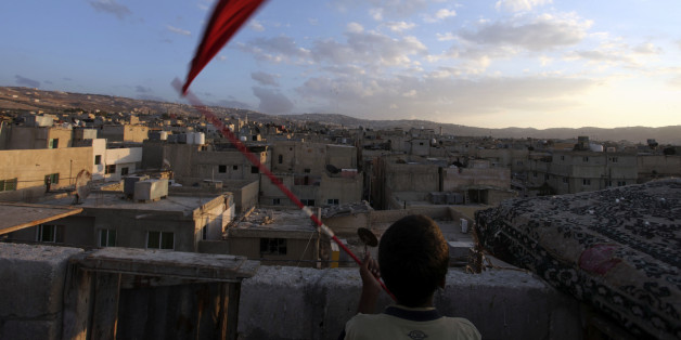 Mohamad Saada, 16, waves a red flag to call his pigeons at al-Baqaa camp, the largest of ten official Palestinian refugee camps north of Amman, Jordan, consisting of over 100,000 residents, Friday, Sept. 23, 2011.  (AP Photo/Mohammad Hannon)