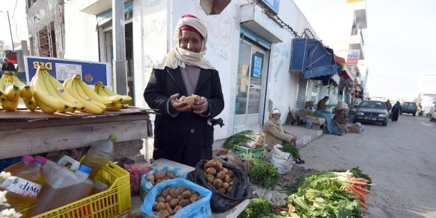 Tunisian vendor Amara Labiadh, 60, poses as he sells white truffles at a market on February 6, 2016 in the town of Ben Guerdane, some 40 kilometres west of the Libyan border.