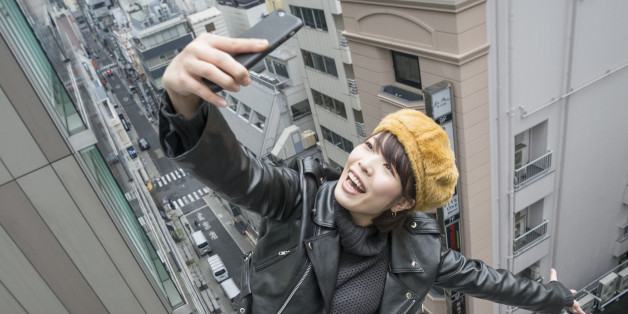 Woman takes dangerous selfie in city.