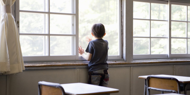 Boy (6-7) looking out of classroom window, rear view