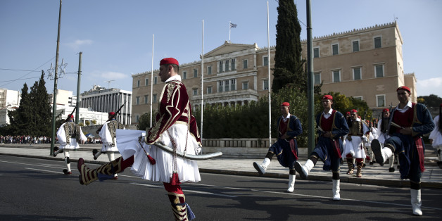 Presidential guards perform ceremonial duties in front of the parliament in Athens, Sunday, Nov. 15, 2015. Greece's government is currently locked in negotiations to reach an agreement on the disbursement of a 2 billion-euro installment ($2.2 billion), as well as 10 billion euros set aside for the recapitalization of its banks. While Greece has met many of the requirements, it remains at odds with creditors over how to deal with non-performing loans and the repossession of homes whose owners have fallen into arrears on mortgage payments. (AP Photo/Yorgos Karahalis)