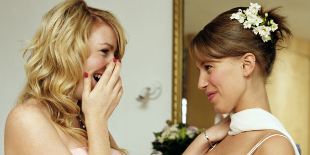 Bride and bridesmaid, laughing, side view