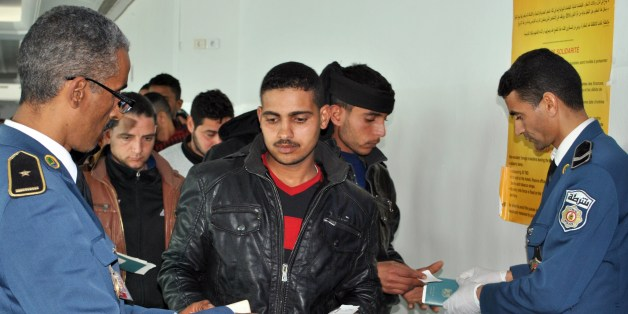 Egyptians, who were formerly residing in Libya, have their documents checked by Tunisian customs at Djerba airport on the Tunisian-Libyan border, before their departure for Cairo, on February 23, 2015. At least 1,000 Egyptians have been evacuated from Libya through Tunisia since February 20, the Tunisian transport ministry said, following the murder of Coptic Christians by the Islamic State group. AFP PHOTO / FETHI NASRI        (Photo credit should read FETHI NASRI/AFP/Getty Images)