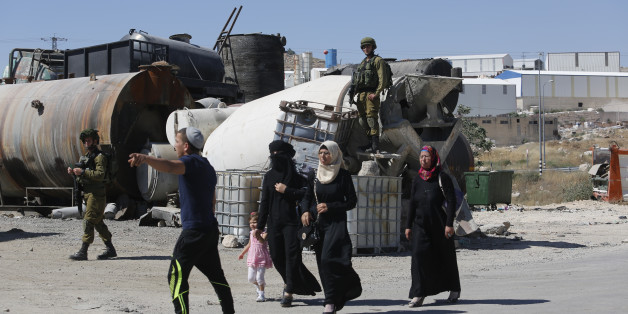 Israeli soldiers prevent Palestinian residents from crossing a security checkpoint at the closed entrance of the West Bank village of Yatta, near Hebron, Thursday, June 9, 2016. Israel on Thursday imposed a series of sweeping restrictions on Palestinian movement and deployed hundreds of additional troops to the West Bank in response to a Tel Aviv attack that killed four Israelis. Israeli police said the two gunmen in their twenties were members of the same family from the Palestinian village of Yatta, one gunman was wounded and was being treated in custody in an Israeli hospital. The other was apprehended by security guards at the scene. (AP Photo/Nasser Shiyoukhi)