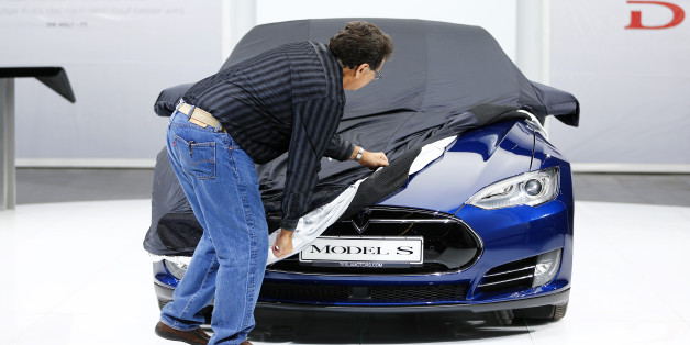 An employee covers a Tesla Model S car during the media day at the Frankfurt Motor Show (IAA) in Frankfurt, Germany, September 14, 2015. Flush with cash and confidence after years of rising sales, German carmakers are used to reaping industry-leading returns. But with Chinese demand abruptly slowing, the profit engine has begun to sputter, overshadowing the glitz of the world's biggest auto show which opens in Frankfurt. REUTERS/Kai Pfaffenbach