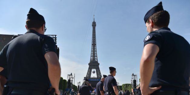 Policemen stand as they watch people gathering in the fan zone behind the Eiffel Tower, on the Champs de Mars during the opening of the Paris fan zone one day before the start of the Euro 2016 football championship, on June 9, 2016.  AFP PHOTO / ALAIN JOCARD / AFP / ALAIN JOCARD        (Photo credit should read ALAIN JOCARD/AFP/Getty Images)