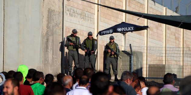 Israeli border police officers stand guard as Palestinians wait to cross through the Qalandia checkpoint to make their way to attend the first Friday prayer of the holy fasting month of Ramadan in Jerusalem's al-Aqsa mosque, near the West Bank city of Ramallah June 10, 2016. REUTERS/Mohamad Torokman
