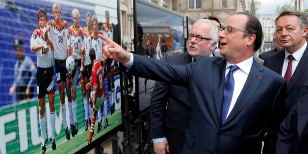 "French President Francois Hollande (2ndL), flanked with French Soccer specialist Pierre Louis Basse (L), comment on a photo of Bulgarian soccer player Hristo Stoitchkov shooting a free kick against Germany in 1994 Euro quarter final during a visit of an exhibition entitled ""Football de Legendes, une Histoire Europeenne"" ('Soccer Legends, a European history'), outside Paris City Hall, in Paris, France, May 9, 2016.    REUTERS/Francois Mori/Pool"