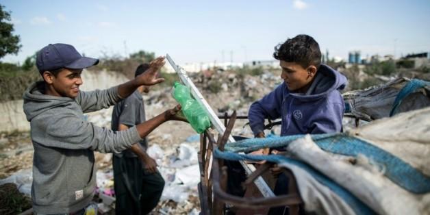 Karam al-Zaaneen, 13 ans et son frère Mustafa, 16 ans, collectent des boutiques en plastique sur une décharge le 18 mai 2016 à Hanun dans le nord de Gaza