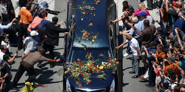 Well-wishers touch the hearse carrying the body of the late boxing champion Muhammad Ali during his funeral procession through Louisville, Kentucky, U.S., June 10, 2016. REUTERS/Adrees Latif     TPX IMAGES OF THE DAY