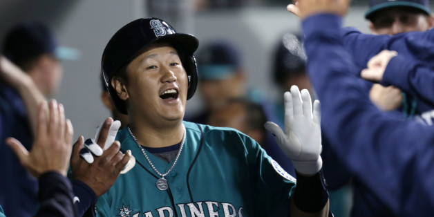 Seattle Mariners' Dae-Ho Lee is congratulated in the dugout after hitting a solo home run on a pitch from Texas Rangers' Derek Holland during second inning of a baseball game on Friday, June 10, 2016, in Seattle. (AP Photo/John Froschauer)