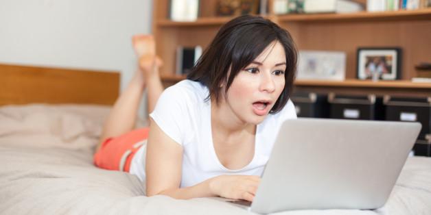 Überraschte Frau vor Laptop