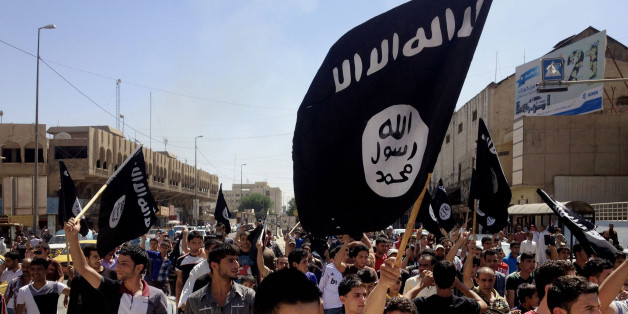 FILE - In this Monday, June 16, 2014 file photo, demonstrators chant pro-Islamic State group slogans as they wave the group's flags in front of the provincial government headquarters in Mosul, 225 miles (360 kilometers) northwest of Baghdad, Iraq. An online image released Wednesday purported to show the Islamic State affiliate in Egypt had beheaded a Croatian hostage.  (AP Photo, File)