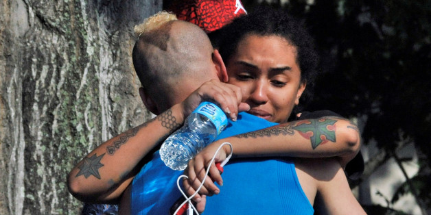 Friends and family members embrace outside the Orlando Police Headquarters during the investigation of a shooting at the Pulse nightclub, where people were killed by a gunman, in Orlando, Florida, U.S June 12, 2016.  REUTERS/Steve Nesius