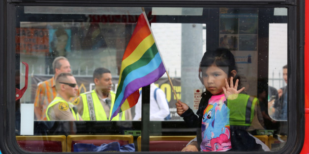 Los Angeles County Sheriff's deputies are seen behind a girl riding in a bus at the 46th annual Los Angeles Gay Pride Parade in West Hollywood, California, after a gunman opened fire at a gay nightclub in Orlando, Florida U.S. June 12, 2016.  REUTERS/David McNew