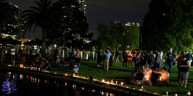 People sit by the water with candles during a vigil in a park following a mass shooting at the Pulse gay nightclub in Orlando, Florida, U.S. June 12, 2016. REUTERS/Carlo Allegri