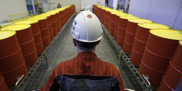 An employee stands in front of lines of oil barrels at Royal Dutch Shell Plc's lubricants blending plant in the town of Torzhok, north-west of Tver, November 7, 2014. Picture taken November 7, 2014. REUTERS/Sergei Karpukhin (RUSSIA - Tags: BUSINESS INDUSTRIAL)