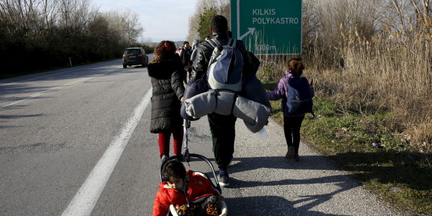A stranded refugee pulls a crib with one of his children as his family walks along a national motorway towards the Greek-Macedonian border near the Greek town of Polykastro after ignoring warnings from Greek authorities that the border is shut, as hundreds of migrants set off on the country's main north-south motorway to Idomeni border crossing February 25, 2016. REUTERS/Yannis Behrakis      TPX IMAGES OF THE DAY