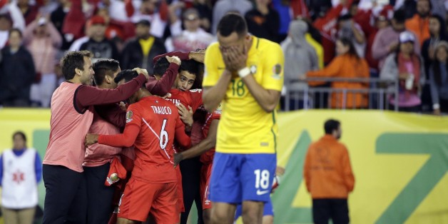 The Peru team celebrates their 1-0 victory as Brazil's Renato Augusto (18) leaves the pitch after a Copa America Group B soccer match between Brazil and Peru Sunday, June 12, 2016, in Foxborough, Mass. (AP Photo/Steven Senne)