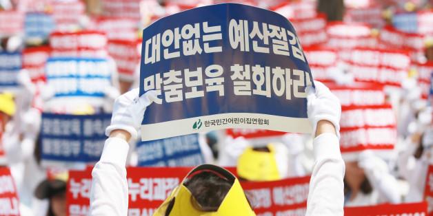 13일 서울 여의도 국회 인근에서 한국민간어린이집연합회 주최로 열린 맞춤형 보육 저지 및 누리과정예산 근본해결 촉구대회에서 참가자들이 손팻말을 흔들고 있다.