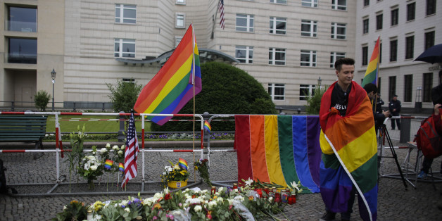 A man stand next to flowers placed in front of the United States embassy during a vigil in Berlin, German, Monday, June 13, 2016 to honor the victims of the attack on the gay nightclub in Orlando, Fla.   (AP Photo/Markus Schreiber)