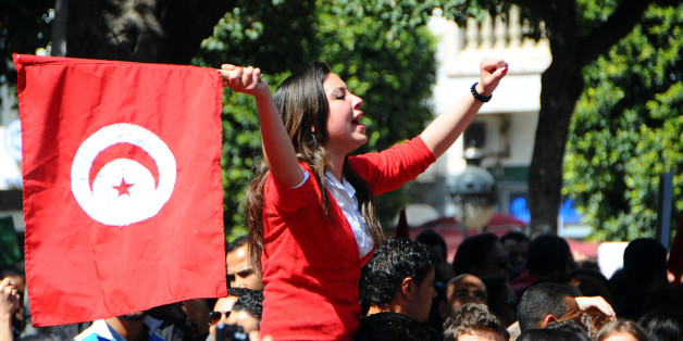 A woman waves a national flag during a demonstration to celebrate Tunisia's independence, Tuesday, March, 20, 2012 in Tunis.  On March 20, 1956, Tunisia achieved independence from France proposed by Habib Bourguiba, who became the first President of the Republic of Tunisia. (AP Photo/Hassene Dridi)