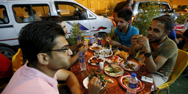 Iraqi youths eat the pre-dawn Suhoor meal before the start of the daily Ramadan fast in a restaurant in Baghdad, July 8, 2015.  The lifting of a night-time curfew in the Iraqi capital five months ago means that, for the first time since the 2003 U.S.-led invasion brought violence and turmoil, lavish Ramadan meals can stretch on until dawn. While the rest of the country fragments, hardline Islamic State fighters battle the army less than 50 km (30 miles) away, and car bombs still regularly inflict their deadly toll across the city, people seize gratefully at any chance to enjoy life.  Picture Taken July 8, 2015.    To match story MIDEAST-CRISIS/BAGHDAD   REUTERS/Thaier Al-Sudani