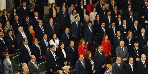 Tunisian parliament members stand during the inaugural session of the newly elected Tunisian parliament in Tunis, Tuesday, Dec. 2, 2014. This is the first national assembly meeting since the October 2014 legislative elections that resulted in a victory for opposition secular parties. (AP Photo/Hassene Dridi)