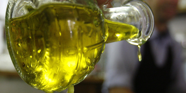 """A diner pours olive oil on a salad at a restaurant in Rome May 17, 2007. When you buy a bottle of olive oil, the rolling Tuscan hills on the label and the """"made in Italy"""" stamp should reassure you the product is as Italian as Chianti or Armani. In fact, there is no guarantee the oil is from Italy. That would change under a bill that forces manufacturers to declare where their oil comes from, meaning many famous brands would have to reveal, for the first time, that most of their """"Italian"""" oil is"""