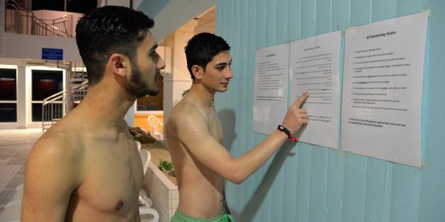 Zwei aus dem Iran geflüchtete junge Männer lesen am 21.01.2016 im Hallenbad in Hermeskeil, Kreis Trier-Saarburg (Rheinland-Pfalz) die Baderegeln, die in deutscher, arabischer und englischer Sprache angebracht sind.