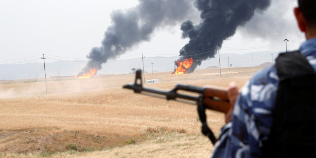 A member of the Kurdish security forces stands guard after explosions at two oil wells in Khabbaz oilfield, 20 km (12 miles) southwest of Kirkuk in Iraq, May 4, 2016. REUTERS/Ako Rasheed