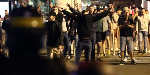 LILLE, FRANCE - JUNE 16: England fans gesture at police officers during clashes aon June 16, 2016 in Lille, France. Police used tear gas and pepper spray on the fans in a bid to keep public order in the city centre this evening.  (Photo by Carl Court/Getty Images)