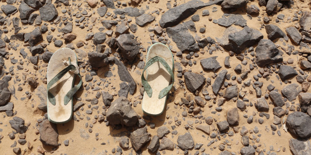 A pair of flip flops, which were left behind by a migrant, lie on the ground in the desert near the border between Algeria and Libya May 29, 2014. Libya's southwestern tip in the Sahara bordering Algeria and Niger has turned into an open door for illegal migrants from sub-Saharan countries heading for Europe, with the chaotic government in Tripoli appearing to have abandoned all control. The revolt that overthrew Libyan leader Muammar Gaddafi three years ago emptied Libya's arsenals, flooded the