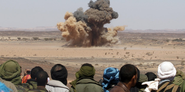 Sahrawis watch a mine explode during a demonstration organised by officials from the Saharawi Arab Democratic Republic (SADR) to show the hazards of mined territory near Tifariti, in the Sahara desert in southwestern Algeria, February 28, 2011. Over 150,000 Sahrawis live in several refugee camps dispersed in the Algerian desert 35 years after Morocco annexed the disputed territory of Western Sahara. REUTERS/Juan Medina (ALGERIA - Tags: POLITICS CIVIL UNREST MILITARY IMAGES OF THE DAY)