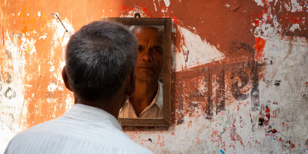 KOLKATA, WEST BENGAL, INDIA, CALCUTTA, WEST BENGAL, INDIA - 2011/10/31: Man looking at the mirror in a street barbershop in Kolkata (Calcutta). West Bengal, India. (Photo by Marji Lang/LightRocket via Getty Images)