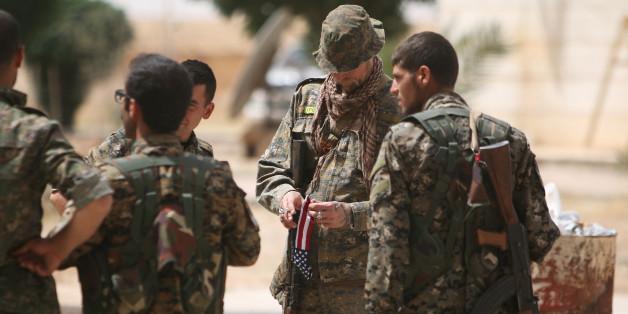 Ein US-Soldat zwischen Kämpfern der SDF