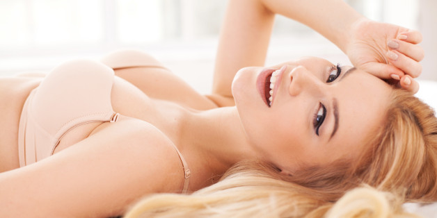 Side view of cheerful and attractive young woman in lingerie lying in bed and smiling at camera