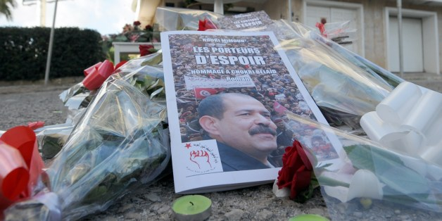 Flowers are laid at a memorial for slain opposition leader Chokri Belaid (portrait) set up at the site where he was murdered one year ago, on February 6, 2014 in Tunis. Tunisians today marked 12 turbulent months since the assassination of opposition politician Chokri Belaid, with his family still demanding to know what happened despite the alleged assassin being shot dead this week. AFP PHOTO / FETHI BELAID        (Photo credit should read FETHI BELAID/AFP/Getty Images)