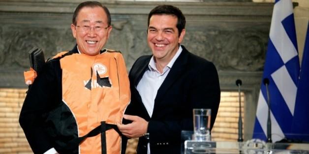 """Le secrétaire général de l'ONU Ban Ki-moon (g) en gilet de sauvetage offert par le Premier ministre grec Alexis Tsipras (d) comme un """"symbole"""" des traversées périlleuses des migrants, le 18 juin à Athènes"""