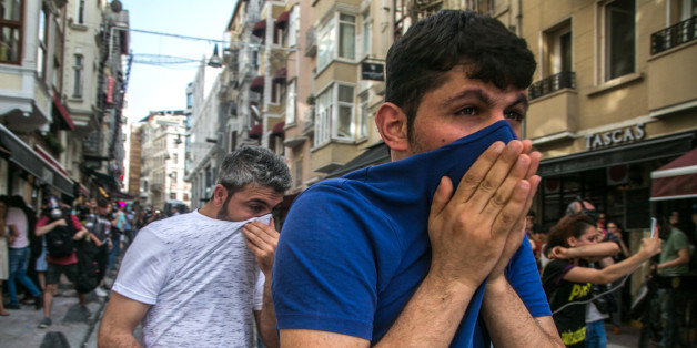 People cover their face with t-shirts as Turkish anti-riot police officers fire rubber bullets to disperse demonstrators gathered for a rally staged by the LGBT community on Istiklal avenue in Istanbul on June 19, 2016. Turkish riot police fired rubber bullets and tear gas to break up a rally staged by the LGBT community in Istanbul on June 19 in defiance of a ban. Several hundred police surrounded the main Taksim Square -- where all demonstrations have been banned since 2013 -- to prevent the 'Trans Pride' event taking place during Ramadan. / AFP / GURCAN OZTURK        (Photo credit should read GURCAN OZTURK/AFP/Getty Images)